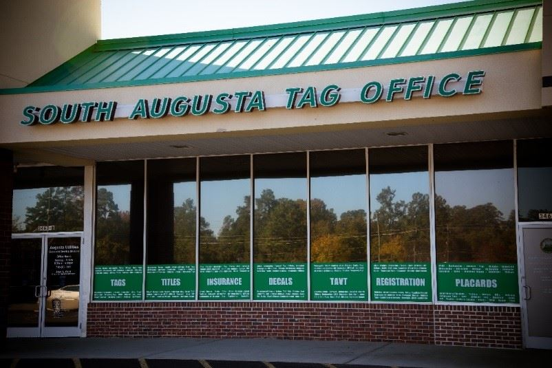 Image of the South Augusta Tag Office facade, with green lettering and a wall of windows